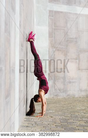 Young Woman Athlete Performs Handstand Exercise On The Street Near The Wall