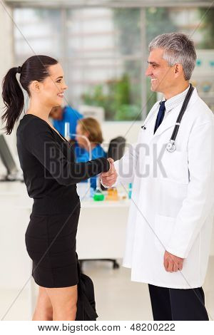 beautiful medical rep handshaking with senior doctor
