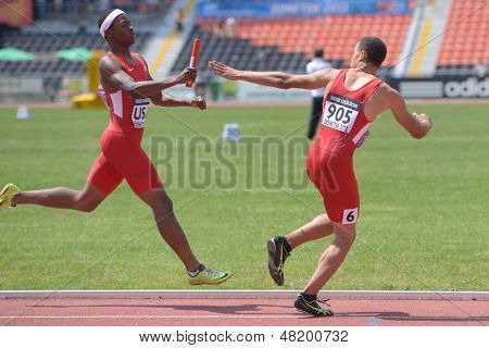 DONETSK, UKRAINE - JULY 13: USA team member Ryan Clark (left) pass the baton to Taylor McLaughlin in the boys medley relay during World Youth Championships in Donetsk, Ukraine on July 13, 2013