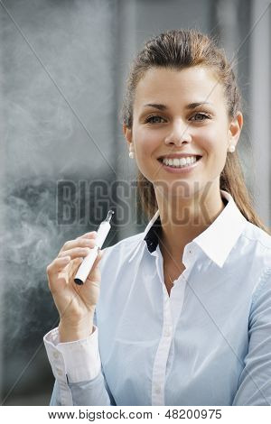 Portrait Of Young Woman Smoking Electronic Cigarette Outdoor Office