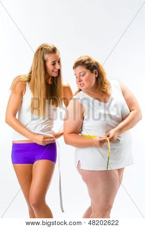Thin and fat woman measuring waist with measuring tape, one woman looking unhappy or envious, studio shot isolated on white