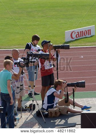 DONETSK, UKRAINE - JULY 12: Photographers film the competition in triple jump during 8th IAAF World Youth Championships in Donetsk, Ukraine on July 12, 2013