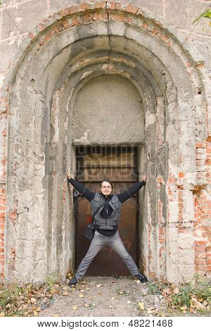 Man Standing In Old Arched Door