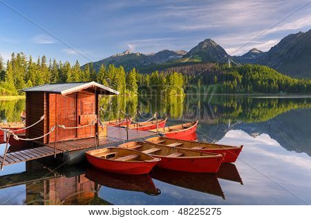 Beautiful red boat in a mountain lake Strbske Pleso, Slovakia, Europe poster