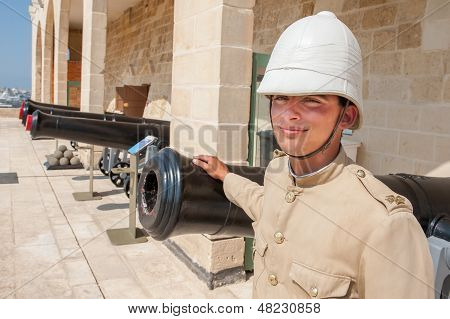 Boy Dressed As In Old English Military Uniform In Front Of The Cannons In Valletta, Malta