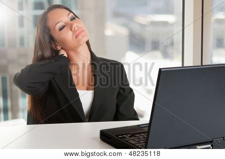 Businesswoman Sitting At Her Desk Tired