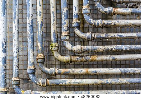 Series of parallel old pipes on wall poster