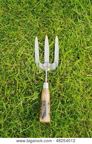 Worn Metal And Wooden Hand Fork On Grass