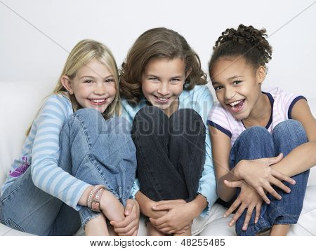 Portrait of three cheerful young friends sitting side by side with knees tucked