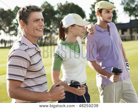 Three young golfers standing on golf course