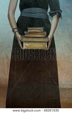 closeup of antique torn books with a hands of a young woman held against black dress on a grunge textured background