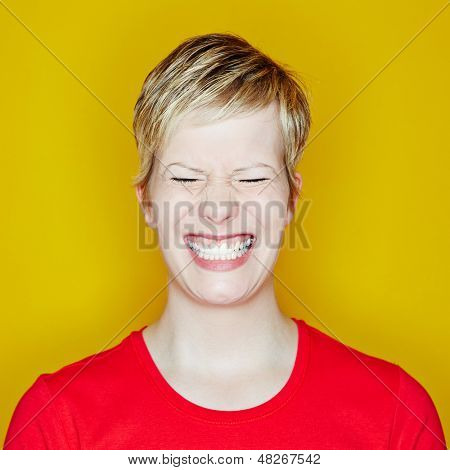 Grining young woman with her eyes closed on a yellow background