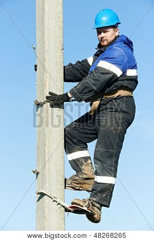 Electrician lineman repairman worker at climbing work on electric post power pole poster
