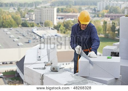 construction mason worker bricklayer working with limestone brick with trowel putty knife outdoors