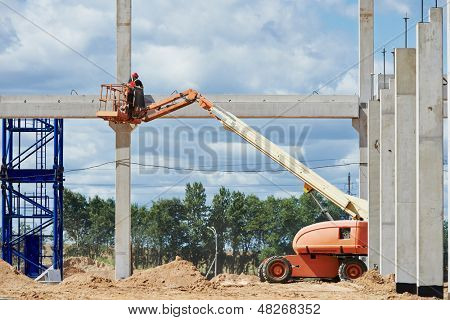 builder worker putting cement mortar on concrete pole joint at construction site using lifting boom machinery poster