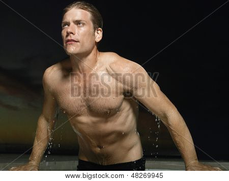 Portrait of a macho young man emerging from water