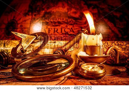 Vintage compass, magnifying glass, pocket watch, spyglass lie on an old ancient map with a lit candle. Vintage still life.