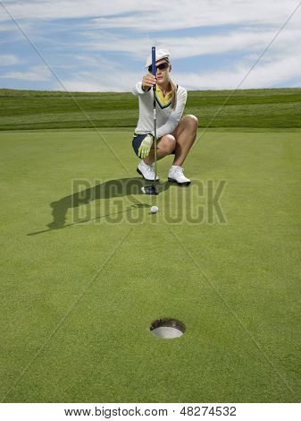 Full length of female golfer lining up a putt in golf course