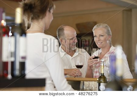 Happy middle aged couple tasting wine with merchant in foreground