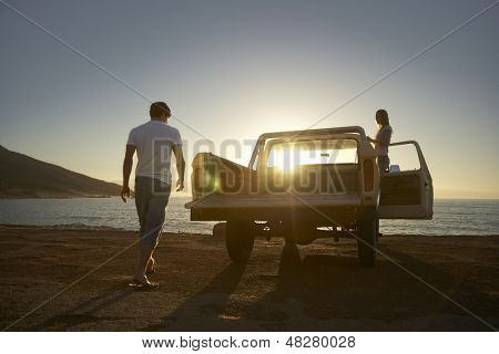 Full length of young couple by pick-up truck parked on beach poster