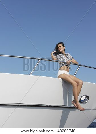 Full length of young woman sitting at edge of yacht with legs dangling overboard