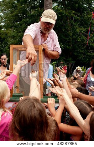 Man Releases Butterflies To Youthful Spectators At Summer Festival