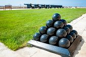 Old cannonballs stacked in pyramid in front of blured cannons on Valletta Castle Malta poster