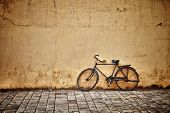 Old rusty vintage bicycle near the concrete wall poster