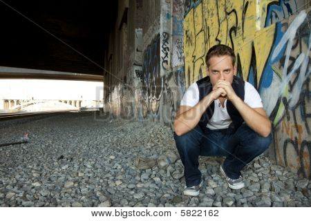 Young Man Kneeling Next To Train Tracks
