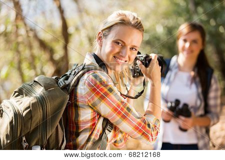 pretty young woman taking photos of her friend in autumn mountain
