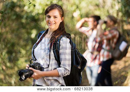 beautiful young woman climbing mountain with friends