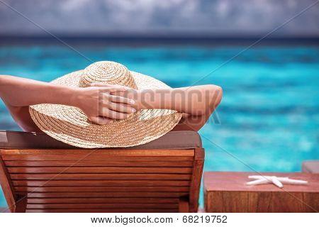 Luxury female tanning on the beach, wearing big stylish hat, enjoying beautiful seascape, summer fashion, travel and tourism concept