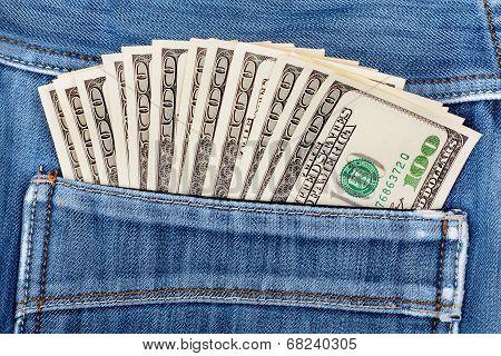A Hundred Dollar Bills Sticking In The Back Pocket Of Denim Blue Jeans
