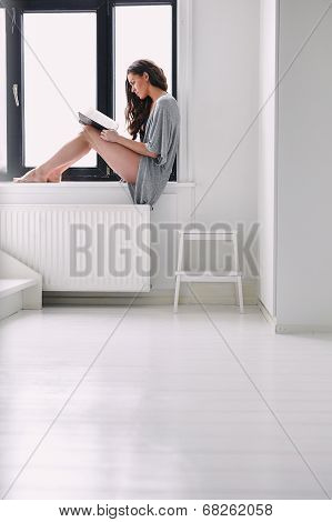 Young Woman Sitting On Window Sill Reading A Book