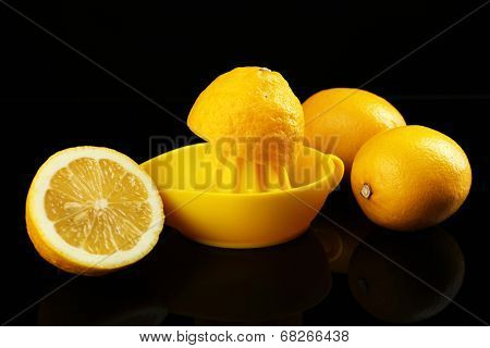 Citrus squeezer with lemons on black background poster