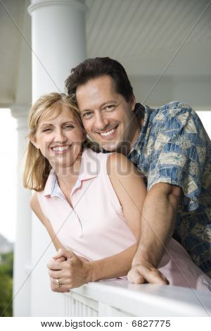 Happy Couple On Porch Of Home