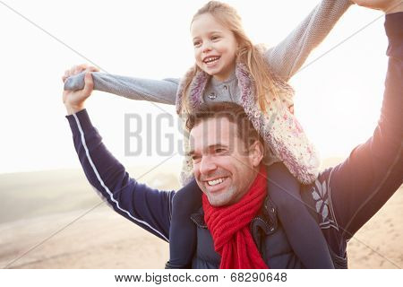 Father And Daughter Walking On Winter Beach
