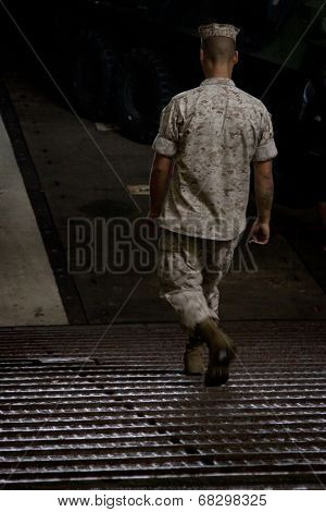 NEW YORK - MAY 22: A sailor walks down a metal ramp to the well deck of the amphibious dock landing ship USS Oak Hill (LSD 51) moored at Pier 92 during Fleet Week NY on May 22, 2014.