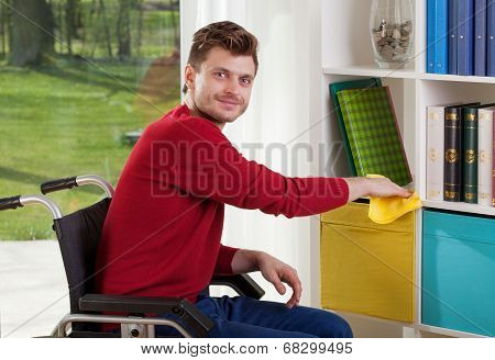 Capable of disabled man wipes the dust on the shelf poster