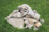 A pile of rough rocks on the green grass photo poster