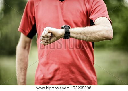 Runner on mountain trail looking at sportwatch smartwatch checking performance gps navigation position map or heart rate pulse trace. Sport and fitness outdoors in nature. poster