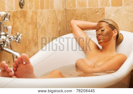 Woman relaxing in a bath with chocolate mask on her face.