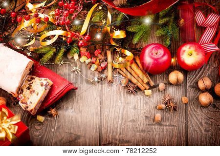 Christmas food border design. Christmas Stollen. Traditional Sweet Fruit Loaf. Xmas holiday table setting, decorated with garlands, baubles, wallnuts, hazelnuts, cinnamon sticks. Warm colors toned.