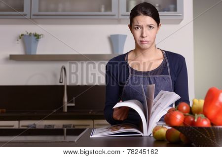 Sad Woman Holding Recipe Book At The Kitchen