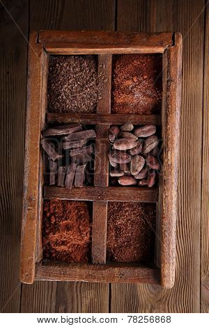 old spicy box full of chocolate - cocoa and sugar, cocoa beans, grated chocolate, hot chocolate flakes, solid pieces, dark cocoa powder