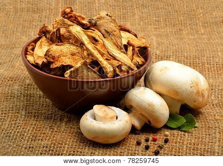 Dried Mushrooms In The Bawl, Ceps And Raw Champignons On The Sacking Background
