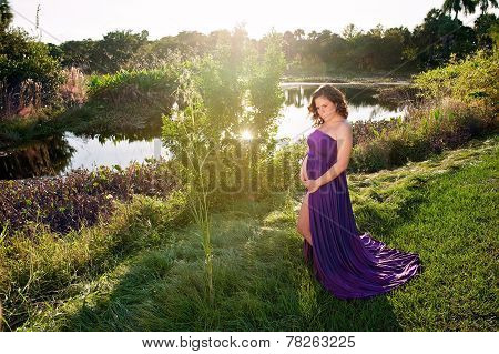 Maternity Portrait Of A Woman Near A Lake's Edge