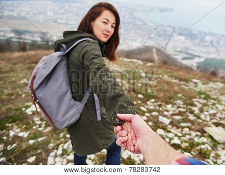 Young traveler woman holding man's hand and leading him on nature. Couple in love poster