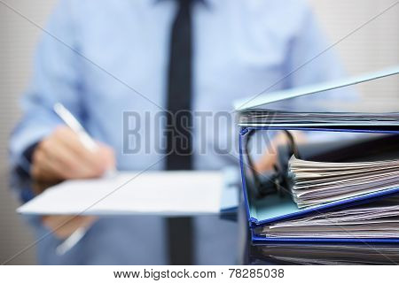 Binders With Papers Are Waiting To Be Processed With Businessman  Back In Blur. Accounting And Busin