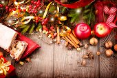 Christmas food border design. Christmas Stollen. Traditional Sweet Fruit Loaf. Xmas holiday table setting, decorated with garlands, baubles, wallnuts, hazelnuts, cinnamon sticks. Warm colors toned.  poster